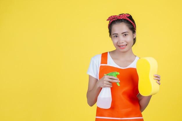 Reinigung eine schöne frau mit einem reinigungsgerät auf einem gelb. Kostenlose Fotos