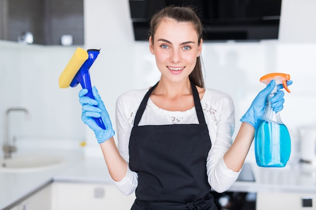 Reinigungskonzept. junge frau, die reinigungswerkzeuge in der küche hält Kostenlose Fotos