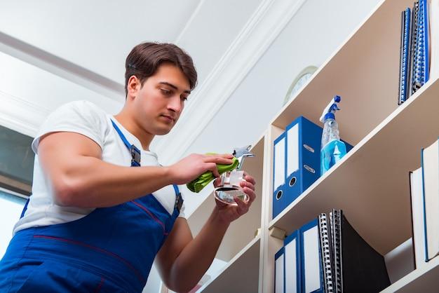 Reinigungsregale des männlichen büroreinigers im büro Premium Fotos