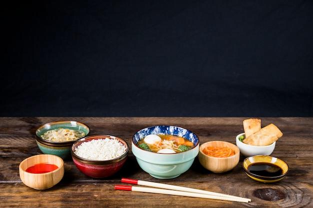 Reis; gekeimte bohnen; frühlingsrollen; fischballsuppe und -soßen mit stäbchen auf tisch vor schwarzem hintergrund Kostenlose Fotos