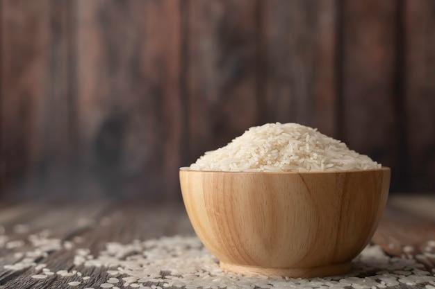 Reis in einer braunen schüssel auf dem holztisch Premium Fotos