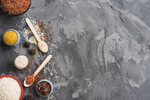 Reis; kurkumapulver; sternanis und pfefferkorn auf schwarzem verwittertem hintergrund mit platz für text Kostenlose Fotos