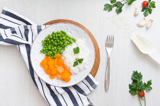 Reis mit gemüse auf hölzernem brett nahe serviette und gabel Kostenlose Fotos
