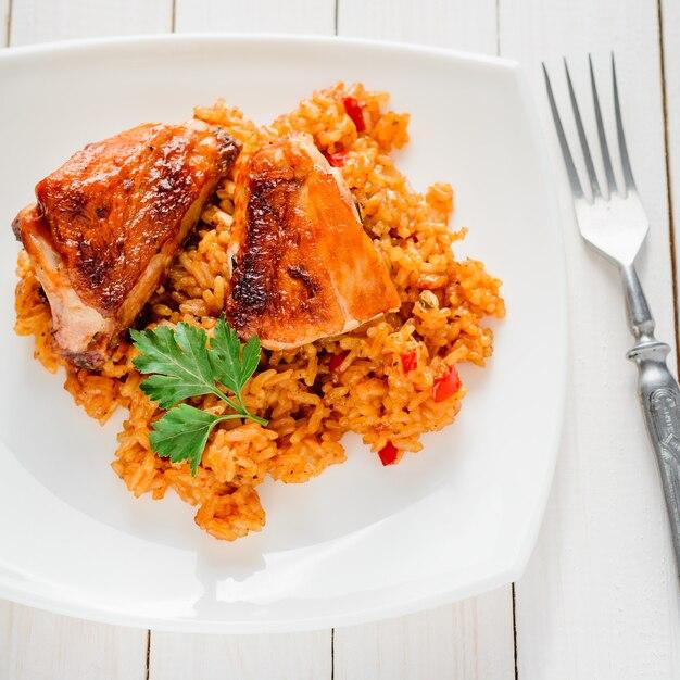 Reis mit gemüse und gebackenem huhn in einer platte auf einer weißen tabelle Premium Fotos