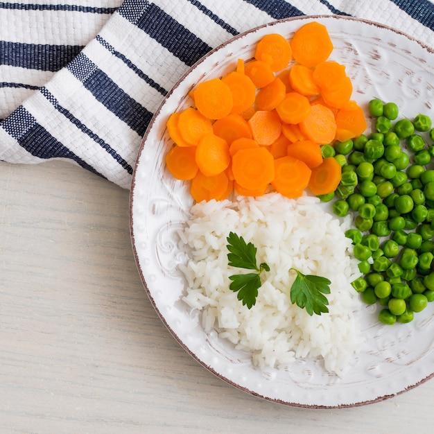 Reis mit gemüse und petersilie auf weißer platte Kostenlose Fotos