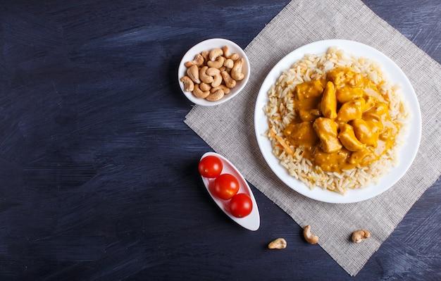 Reis mit hühnercurrysoße mit acajoubaum auf schwarzer holzoberfläche. Premium Fotos