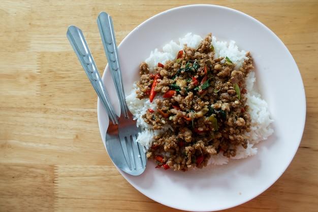 Reis überstieg mit angebratenem schweinefleisch und basilikum im weißen teller auf holztisch. Premium Fotos