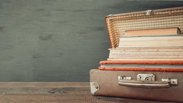 Reise-lederkoffer der weinlese alte klassische mit stapel alten büchern Premium Fotos
