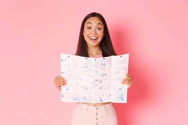Reise-, lifestyle- und tourismuskonzept. fröhliche, attraktive asiatische mädchen tourist erkunden neue stadt, besuchen museen, zeigen karte der stadt mit sehenswürdigkeiten und lächelnden optimistischen, rosa hintergrund. Kostenlose Fotos
