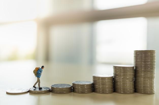 Reise-, spar- und planungskonzept. schließen sie oben von reisenden miniaturfigur menschen mit rucksack, die oben auf stapel von münzen mit kopienraum gehen. Premium Fotos