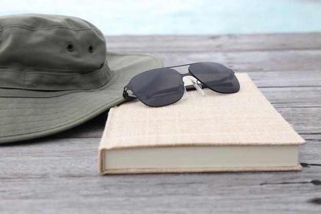 Reise- und ferienkonzept der kamerasonnenbrille und -buches auf dem bretterboden Premium Fotos