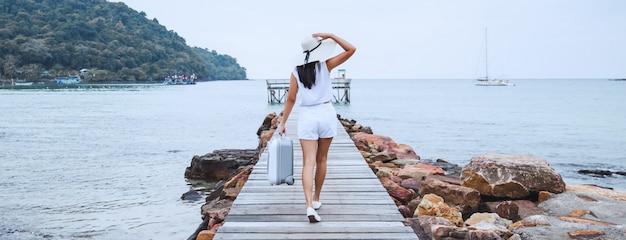 Reisefrau mit koffer am strand Premium Fotos