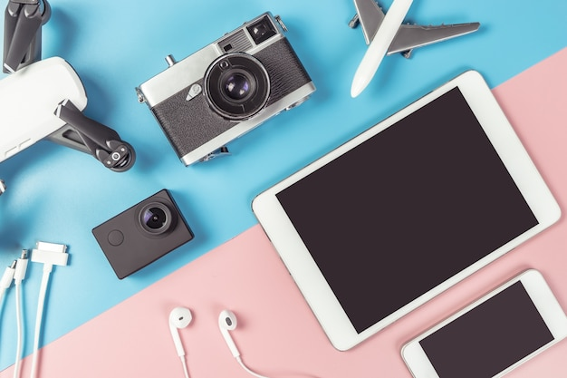Reisegeräte flatlay auf blauem und rosa hintergrund für reisekonzept Premium Fotos
