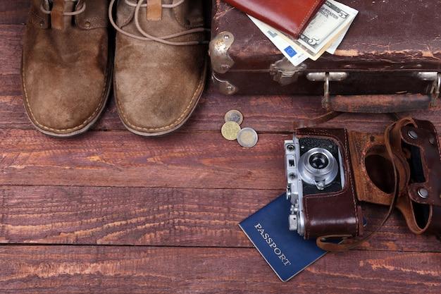 Reisekonzept mit weinlesekoffer, sonnenbrille, alter kamera, velourslederstiefeln, fall für geld und pass auf bretterboden. Premium Fotos