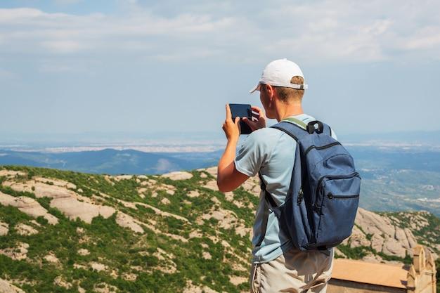 Reisemann mit rucksackstellung machen ein foto durch sonnigen tag des smartphone mountians kopienraum Premium Fotos
