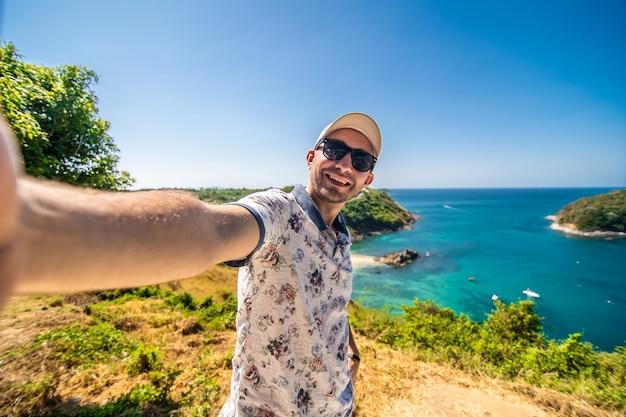 Reisen junger mann stehend machen ein foto mit smartphone und sehen schöne landschaft landschaft naturansicht auf rock mountain in phuket thailand. Premium Fotos