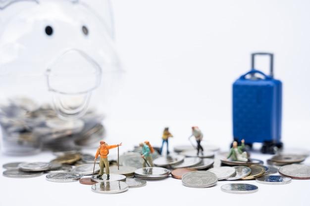 Reisen und sparen. miniaturleute, reisende mit rucksack gehend auf münzenstapel und sparschwein und gepäck als hintergrund. Premium Fotos