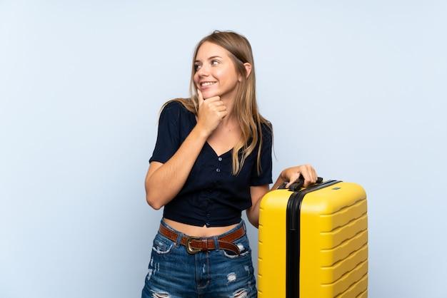 Reisendblondine mit koffer eine idee denkend und seite schauend Premium Fotos