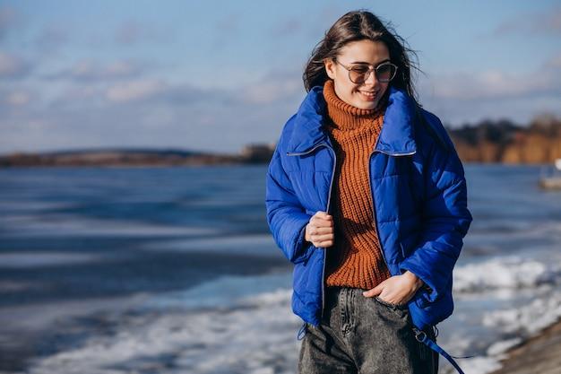 Reisende der jungen frau in der blauen jacke auf dem strand Kostenlose Fotos