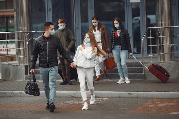 Reisende, die den flughafen verlassen, tragen schutzmasken Kostenlose Fotos