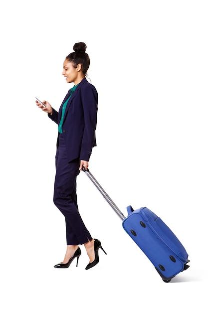 Reisende geschäftsfrau, die mit tasche und handy geht Premium Fotos