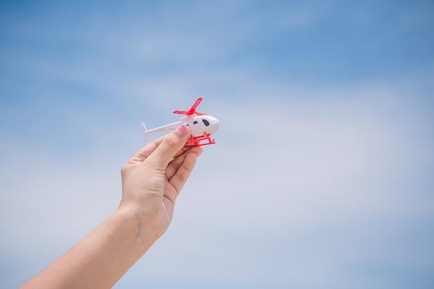 Reisende menschen konzept. hand zeigt den hubschrauber am himmel Premium Fotos