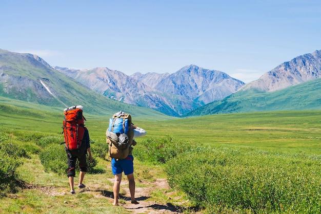 Reisende mit großen rucksäcken fahren im grünen tal hinauf zu riesigen bergen Premium Fotos