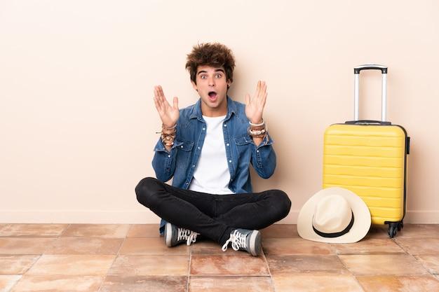 Reisender bemannen seinen koffer, der auf dem boden mit überraschungsgesichtsausdruck sitzt Premium Fotos