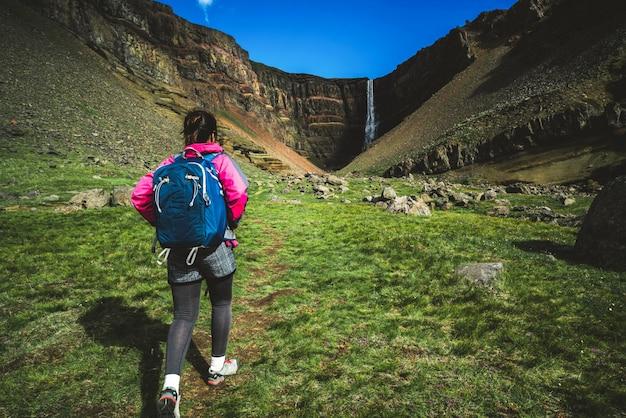 Reisender, der am hengifoss wasserfall, island wandert. Premium Fotos