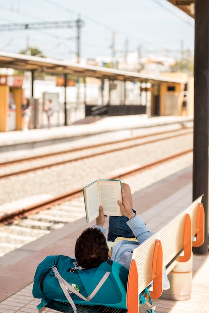 Reisender, der ein buch liest und auf zug wartet Kostenlose Fotos