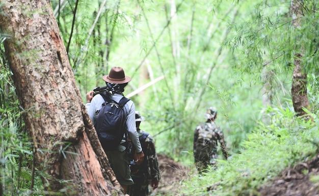 Reisender, der in den bambuswald geht mannwanderer-gebirgsgruppe freunde, die mit rucksäcken gehen Premium Fotos