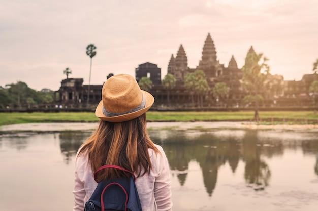 Reisender der jungen frau, der angkor wat, khmerarchitekturerbe betrachtet Premium Fotos