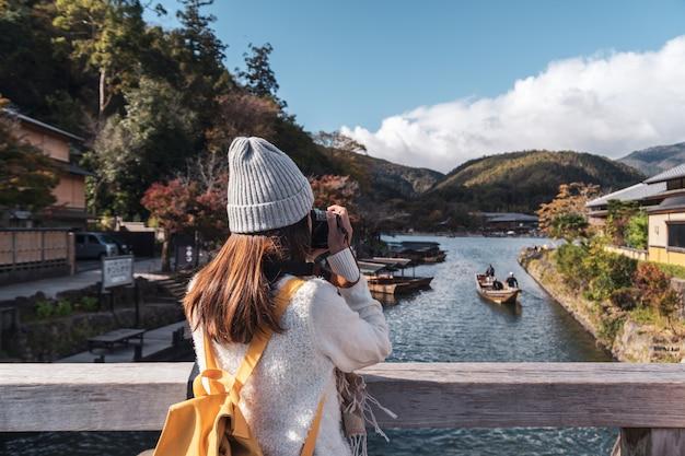Reisender der jungen frau, der schöne landschaft arashiyama japan, reiselebensstilkonzept betrachtet Premium Fotos