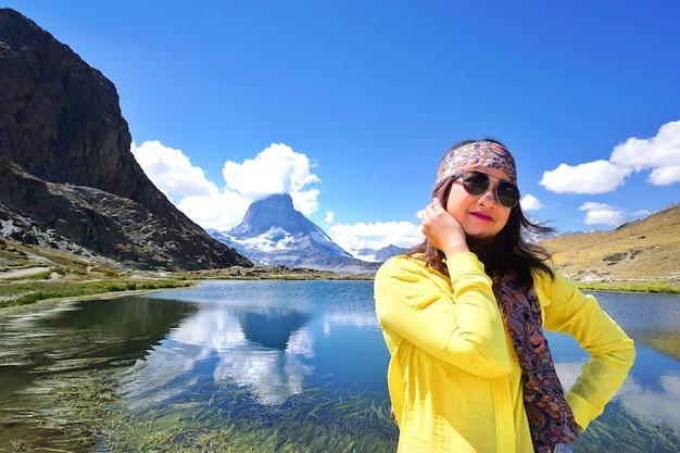 Reisender, der nahe dem alpinen see von riffelhorn vor berg matterhorn-spitze, zermatt, die schweiz steht. Premium Fotos