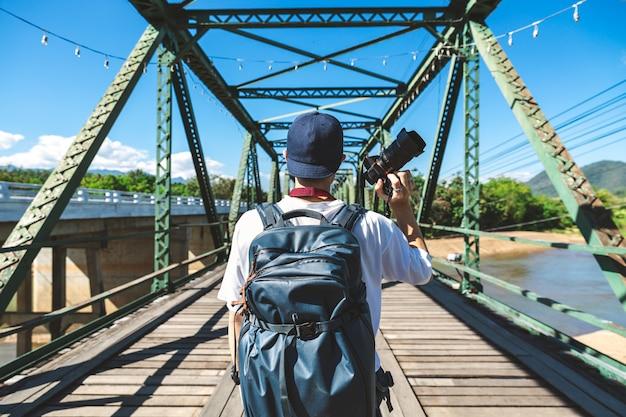 Reisender mann mit kamera auf einer rostigen brücke Premium Fotos
