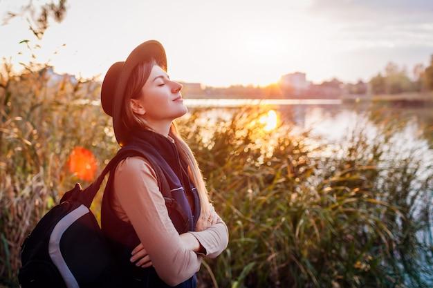 Reisender mit dem rucksack, der durch herbstfluß bei sonnenuntergang sich entspannt. junge frau, die tief atmet, glücklich und frei fühlend Premium Fotos