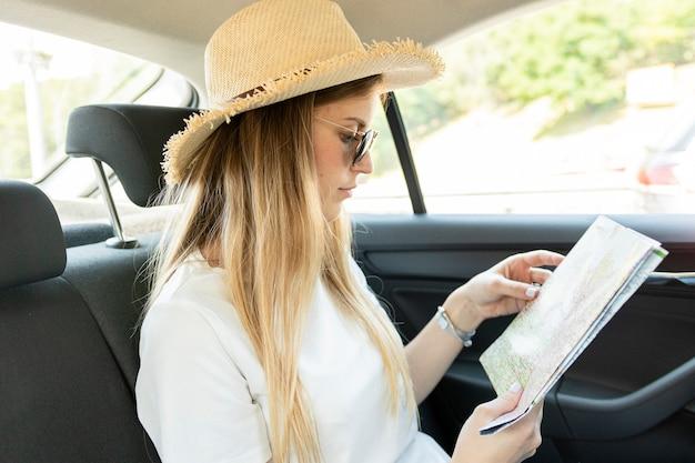 Reisendfrau in einem auto, das karte betrachtet Kostenlose Fotos