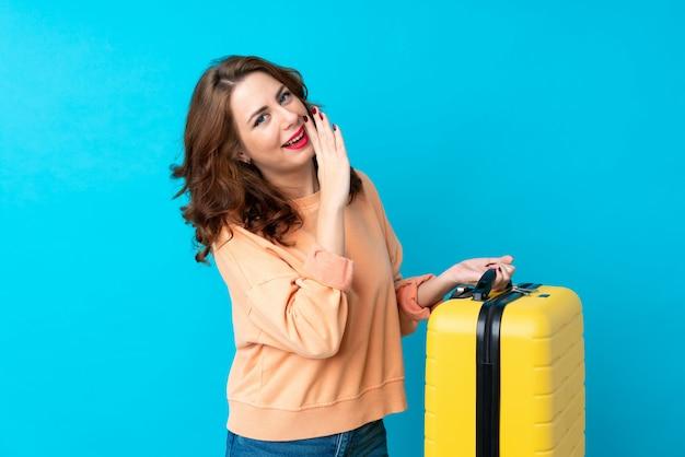 Reisendfrau mit koffer über dem lokalisierten flüstern etwas Premium Fotos