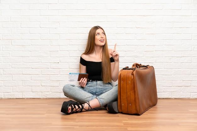 Reisendfrau mit koffer und bordkarte, die beabsichtigt, die lösung beim anheben eines fingers zu verwirklichen Premium Fotos
