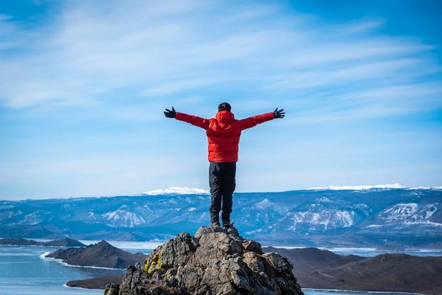 Reisendmann-abnutzungsrotkleidung und anheben des armes, der tagsüber auf berg im baikalsee, sibirien, russland steht. Premium Fotos