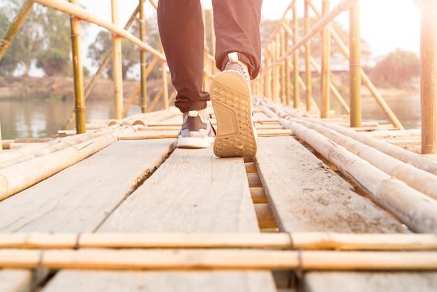Reisendmann, der zum erfolg auf der langen hölzernen bambusbrücke geht Premium Fotos
