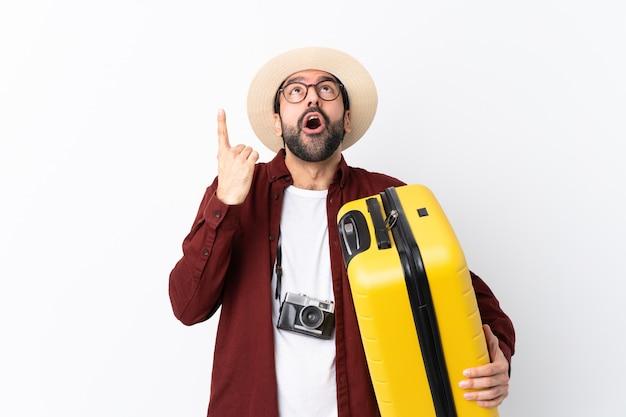 Reisendmannmann mit dem bart, der einen koffer über lokalisierter weißer wand überrascht hält und oben zeigt Premium Fotos