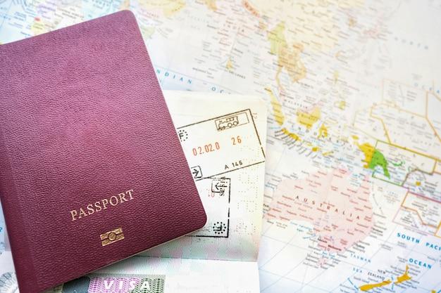 Reisepass auf einer karte der welt. abreise- und ankunftsstempel mit visum. reise-reise-ferien-feiertagskonzept. Premium Fotos