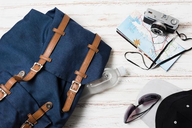 Reisetasche und zubehör auf hölzernem hintergrund Kostenlose Fotos
