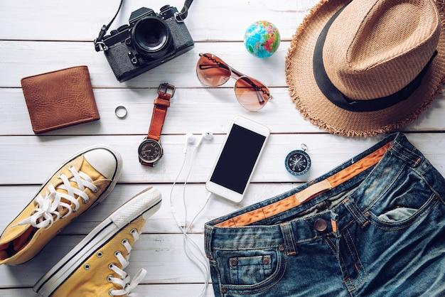 Reisezubehör kostüme. pässe, gepäck, die kosten für reisekarten, die für die reise vorbereitet wurden, auf weißem holzboden Premium Fotos