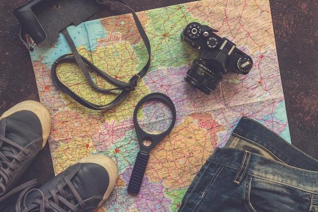 Reisezubehörkamera, strohhut, karte, schuhe, laptop, auf einem draufsichtplan des dunklen hintergrundes flach Premium Fotos