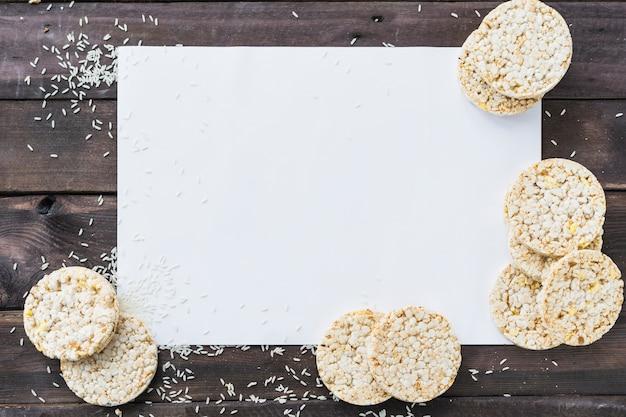 Reiskörner und luftgestoßener reiskuchen auf weißem leerem papier über dem hölzernen schreibtisch Kostenlose Fotos