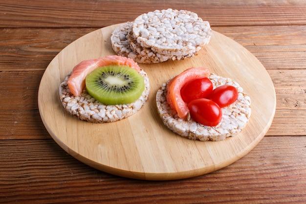 Reiskuchen mit lachs-, kiwi- und kirschtomaten auf holz Premium Fotos