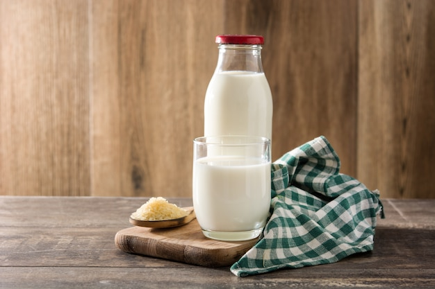 Reismilch im glas und in der flasche auf hölzerner tabelle Premium Fotos