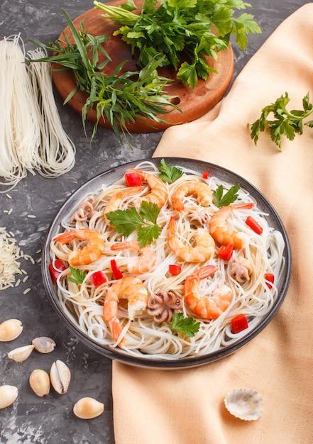 Reisnudeln mit garnelen oder garnelen und kleinen kraken auf grauer keramischer platte auf einem schwarzen konkreten hintergrund Premium Fotos